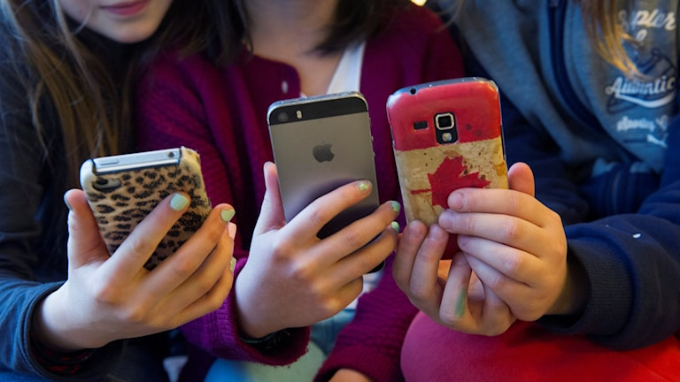 Tre tjejer sitter med varsin mobil i handen.