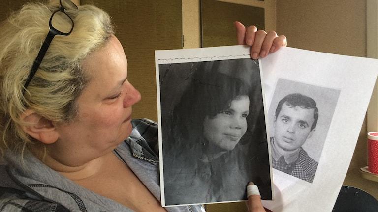 Marie Johansson håller upp två bilder på en man och en kvinna.