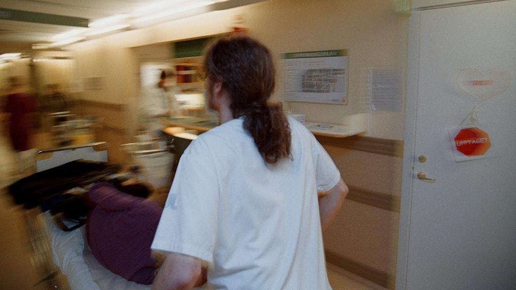 En kvinna går med en patient på sjuksäng genom en sjukhuskorridor.