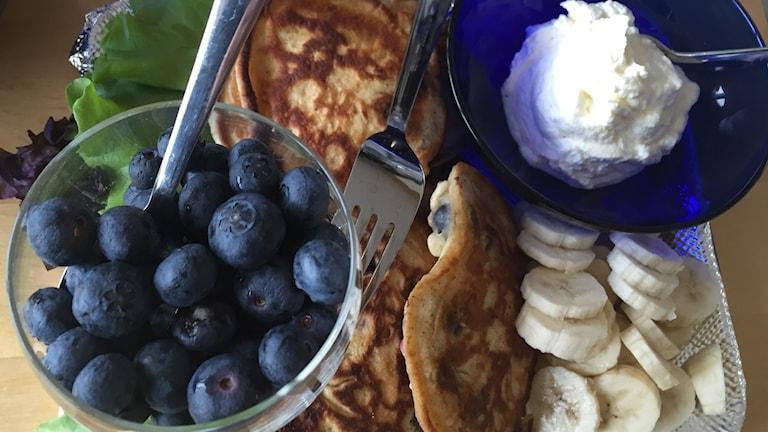 Bilder på pannkakor och blåbär, grädde och banan.