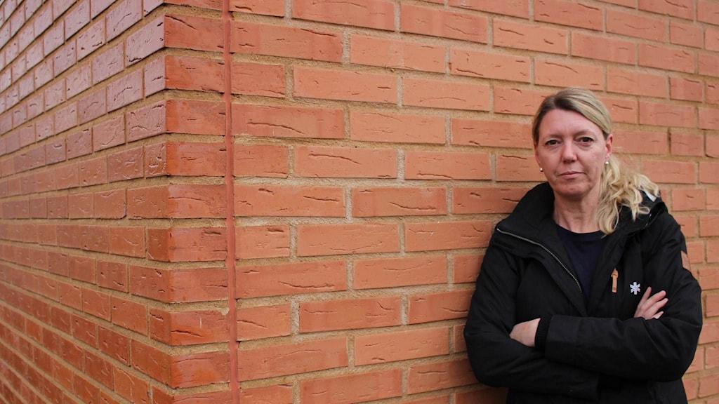 Pernilla står lutad mot en tegelvägg.