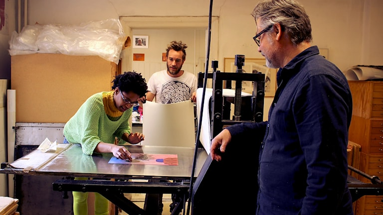 Susana Pilar Delahante Matienzo lägger en kopparplåt på tryckpressen. Daniel Wilhelmsson och Raine Falkås tittar på.