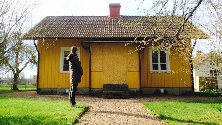 Carolin framför sitt torp som saknar dörrar och fönster till glasverandan