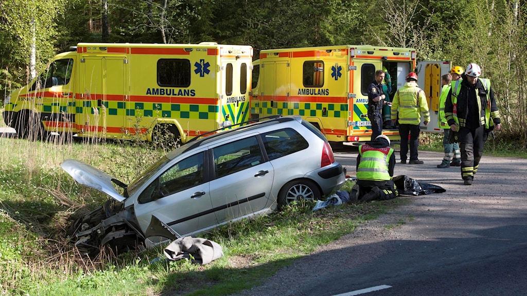 Bil med skador i fronten i dike. Två ambulanser och räddningspersonal.