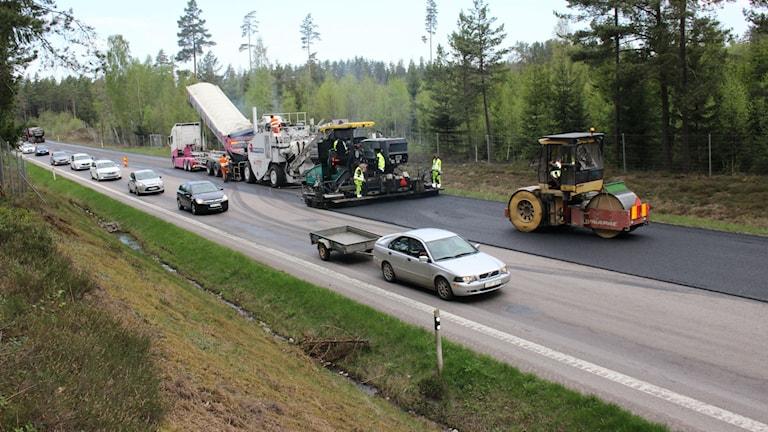 Ett tiotal bilar kör förbi vägarbetarna som lägger asfalt.