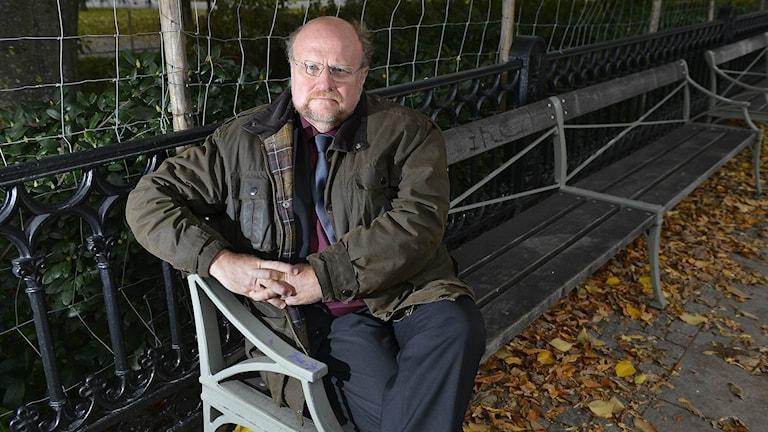 Ola Larsmo sitter på en parkbänk.