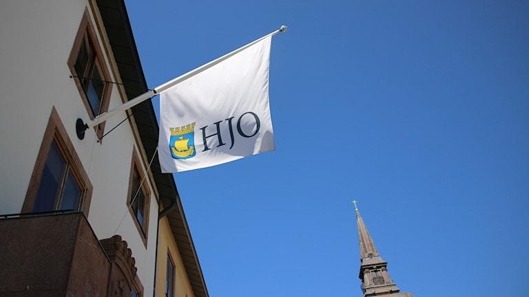En vit flagga med Hjo skrivet på den svajar i vinden utanför kommunhuset.