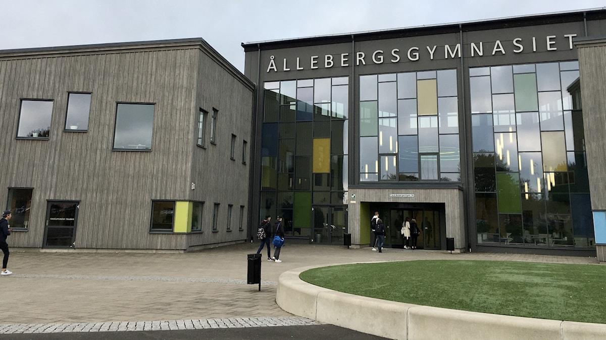Entrén till Ållebergsgymnasiet i Falköping har stora fönster över hela fasaden och gråa byggnader bredvid.