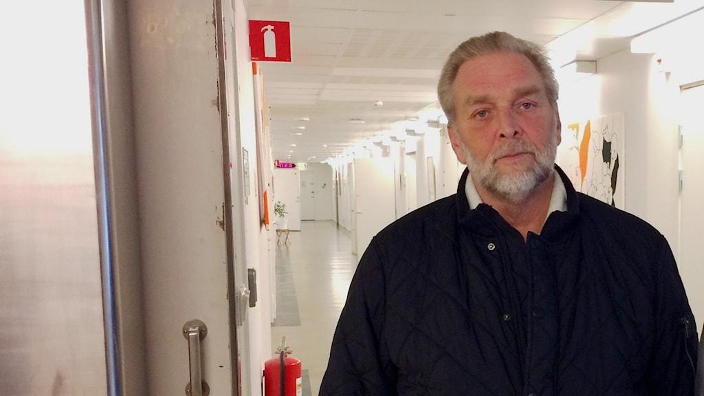 En man står framför en korridor på socialkontoret