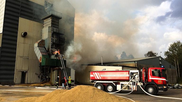 Räddningstjänsten försöker släcka branden i sädessilon i Nossebro.