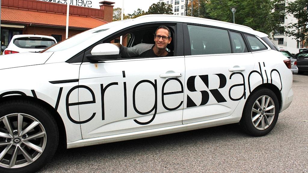 Torbjörn borg sitter i en vit bil som det står Sveriges Radio på.
