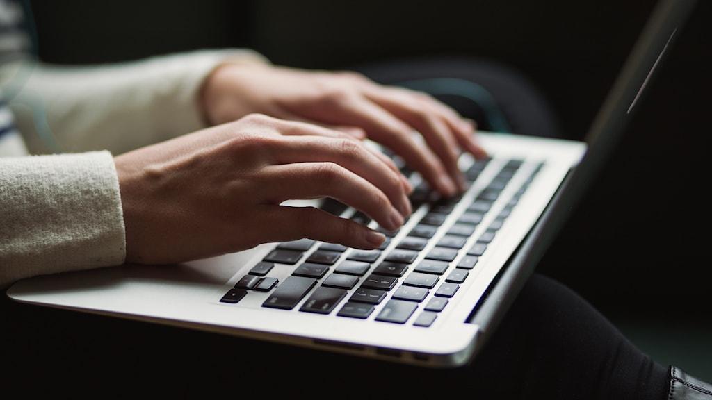 Ett par händer skriver på en bärbar dator.