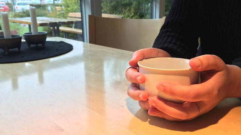 Händer som håller i en kaffekopp över ett bord.
