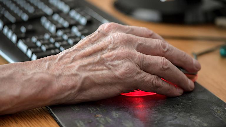 Äldre hand håller i en datormus.