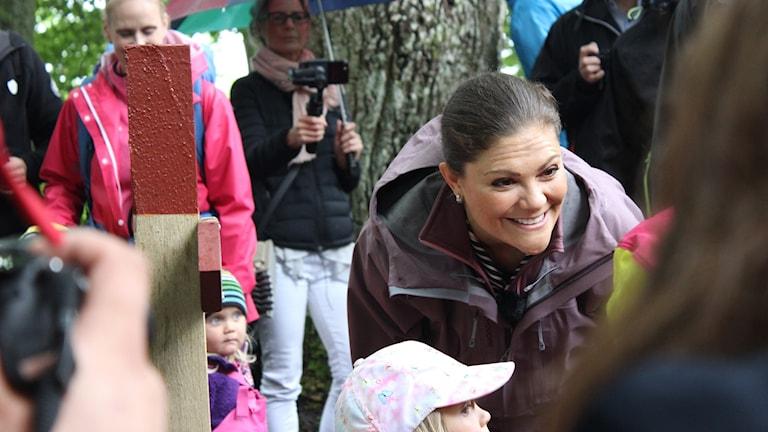 Kronprinsessan ler mot ett barn. Det står många människor runtom henne.