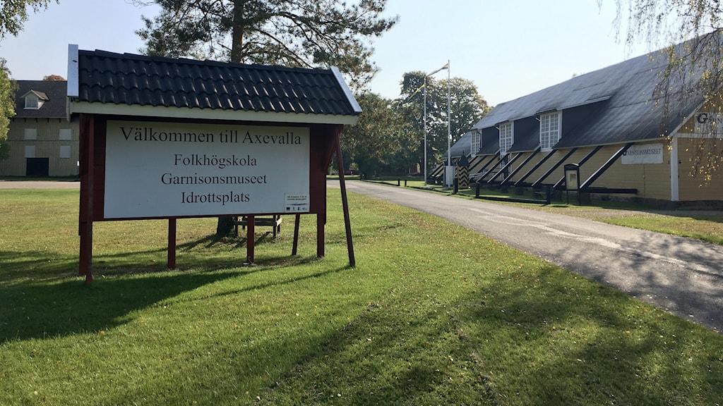 En skylt med texten Välkommen till Axevalla folkhögskola och i bakgrunden syns en gul äldre byggnad.