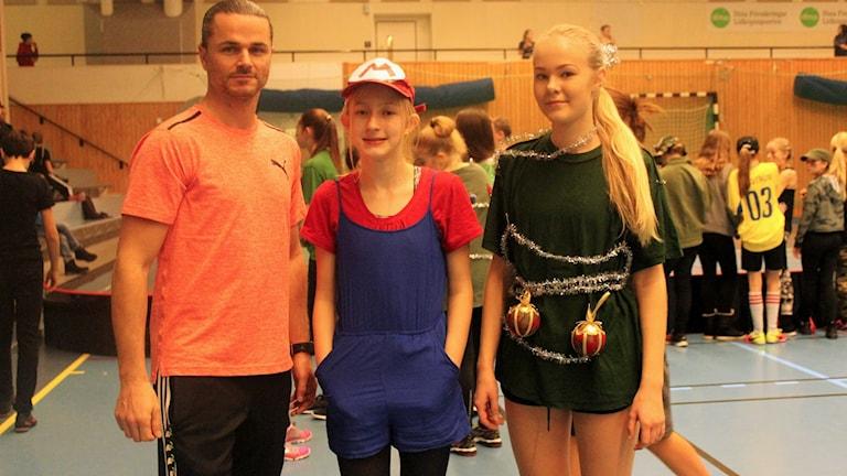 Idrottsläraren Markus Dalemo och eleverna Leia Wolcher och Hanna Larsson från Fredriksdalskolan i Lidköping står inne i Idrottens Hus. De deltar i lussebandy på Luciadagen.