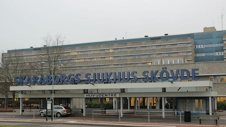 På bilden syns huvudingången till Skaraborgs sjukhus i Skövde. Det är en gråmulen dag. Framför entrén står en taxi. Man ser en del av den stora, gråa huvudbyggnaden i bakgrunden.