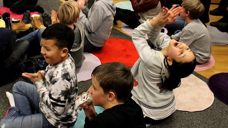 Barn som jublar och klappar händerna