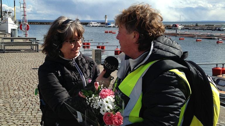 En tårögd Ewa Ohlsson i reflexväst intervjuas av Carina Grönqvist.