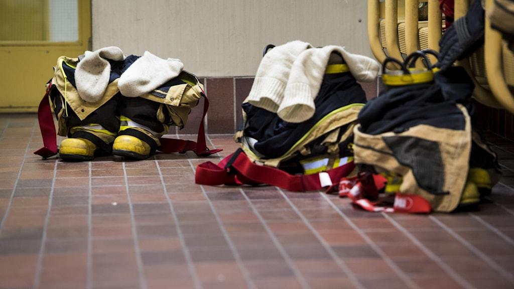 Tre brandmansuniformer ligger på ett klinkergolv i en brandstation.