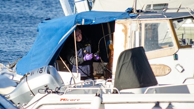 Polisens tekniker inne i en små båt med föremål i hamnen.