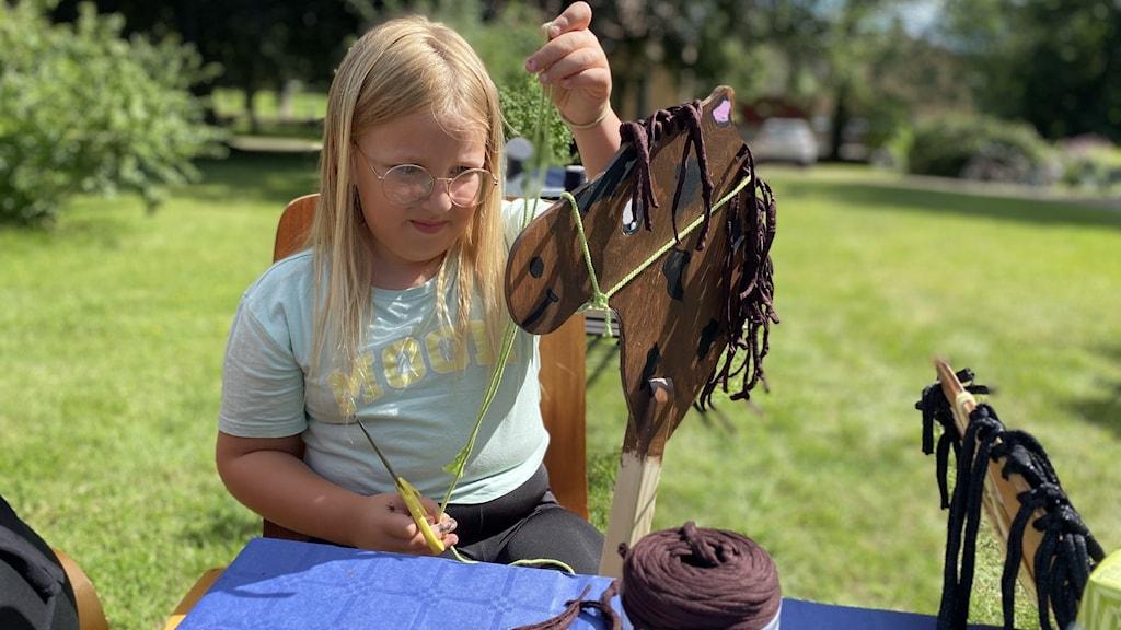 En sjuårig flicka sitter ute i solen och tillverkar en käpphäst.