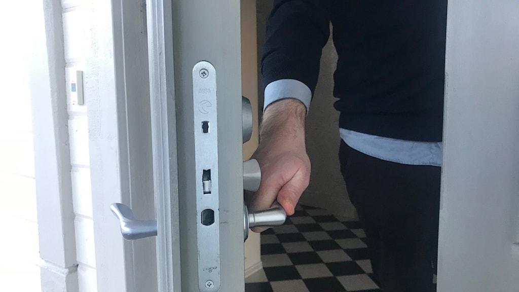 En ytterdörr öppnas, hand på handtag.
