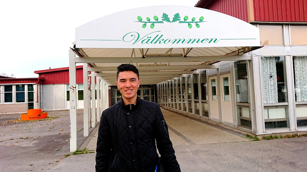 Hameed Bagheri står mitt i bild framför entren till Vadsbogymnasiet.