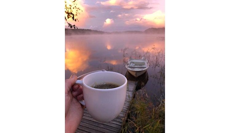 En hand som håller i en kaffekopp framför en sjö
