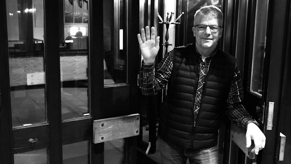 Kyrkogårdsföreståndaren Anders Larsson i Tibro vinkar hej då i dörren till en av kommunens kyrkor.