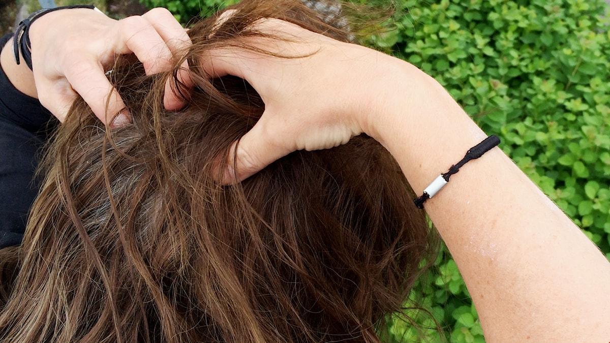 Kvinna som kliar sig i håret på grund av knott
