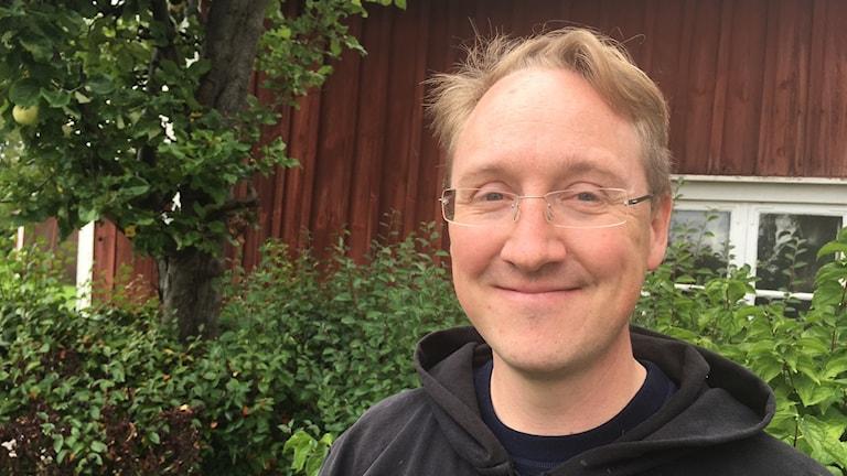 Porträttbild av Martin Toresson. I bakgrunden syns gröna buskar och en röd husvägg.