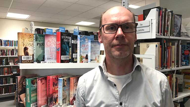 En man står framför en bokhylla fylld av böcker.