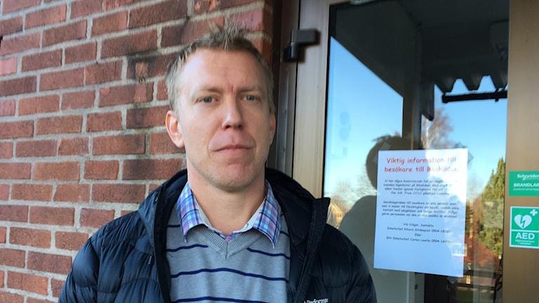 Porträttbild av Rikard Strömqvist framför en entrédörr.