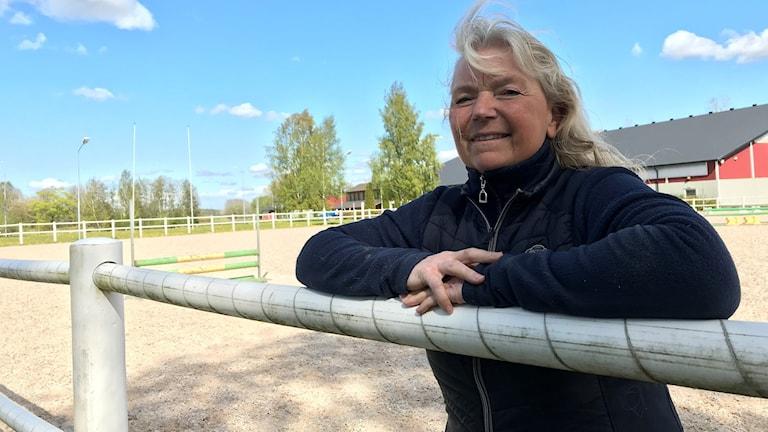 En kvinna hänger över ett staket runt en hästhage.