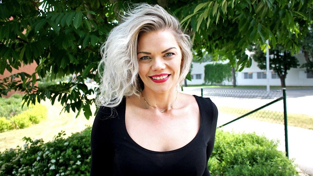 Kvinna med med blont hår som kollar in i kameran och ler