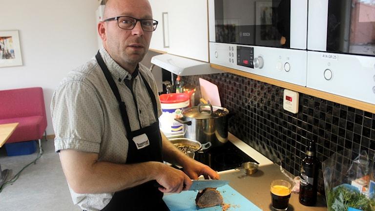 Nicke Kock skär upp kött i P4 Skaraborgs kök.