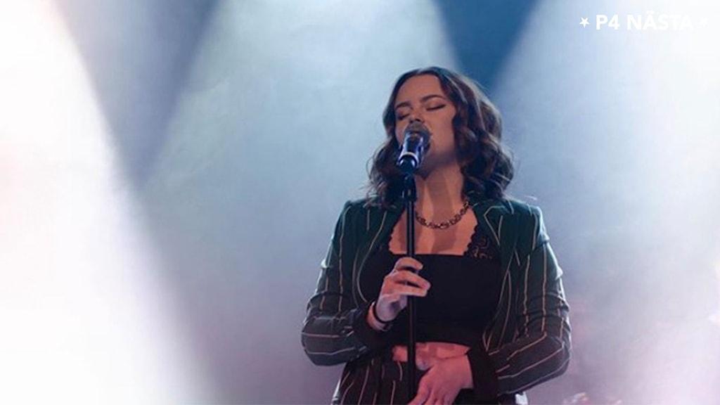 En kvinna sjunger i strålkastarljuset på en scen.
