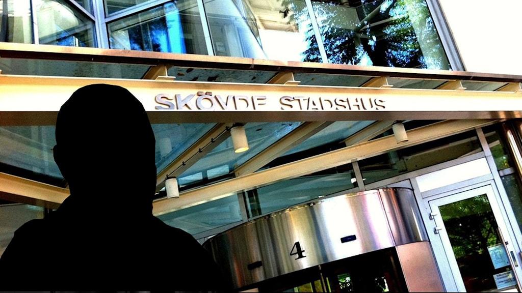 en anonym man framför en bild på Skövde Stadshus