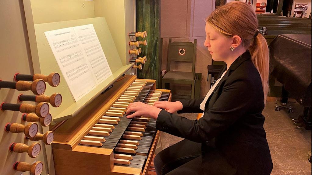 En ung tjej sitter vid en orgel i kyrkan och spelar.