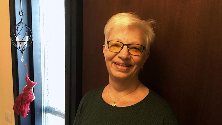 En kvinna med glasögon och en grön tröja.