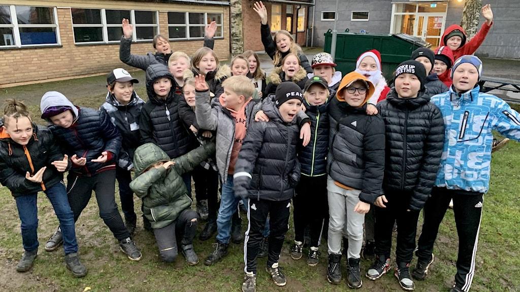 Klass 5 på Vartoftaskolan i Falköpings kommun. Hela klassen är samlad i en gruppbild. Klasskamraterna ler, vinkar till kameran, och håller armarna om varandra.
