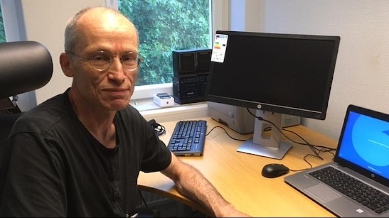 Jack Widmark sitter framför ett skrivbord med två dataskärmar.