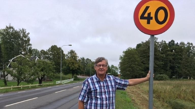 Douglas Pettersson vid sidan av en väg. Håller i en trafikskylt med siffran 40.