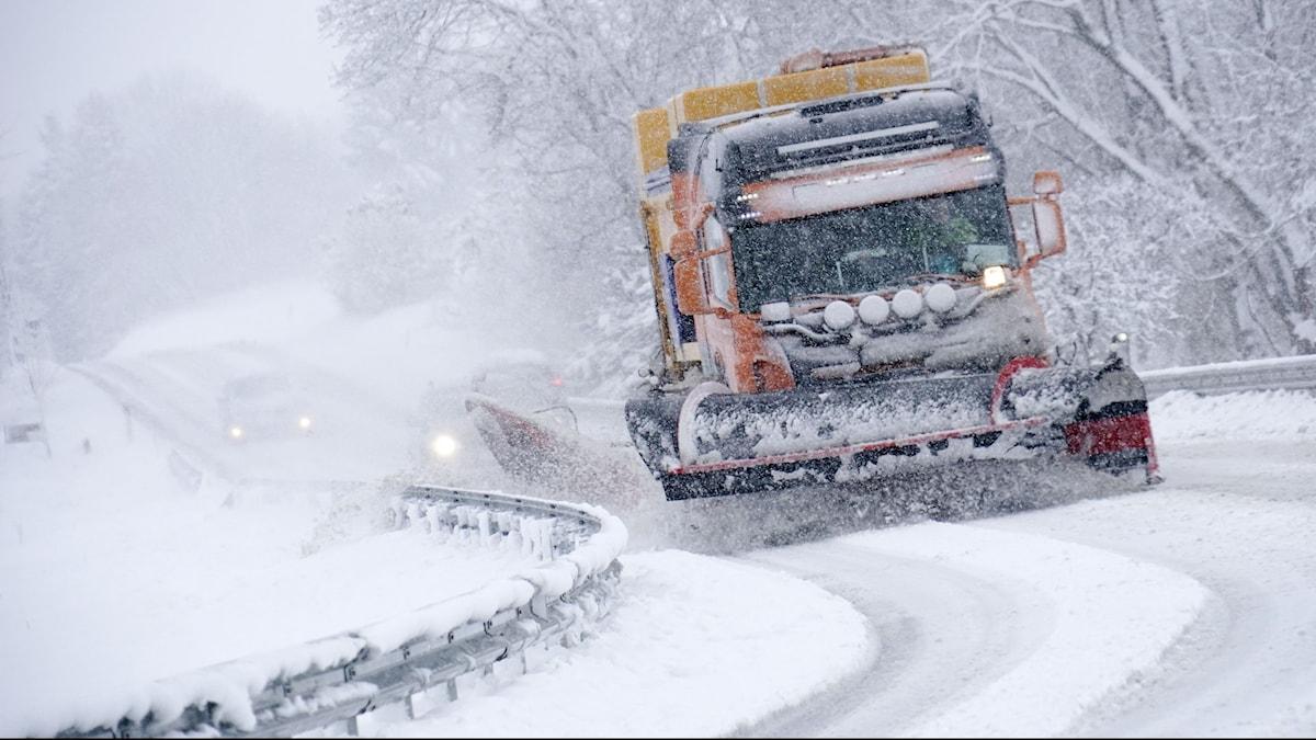 En lastbil med plogblad röjer snö på en snöfylld väg med mitträcke.