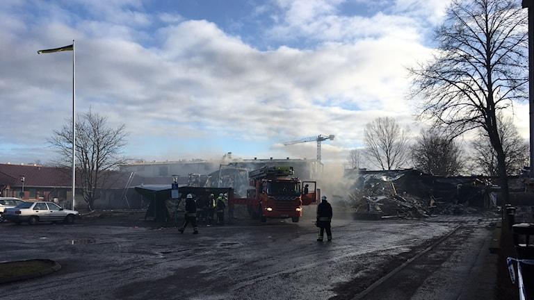 Rök från brandplasten. I förgrunden en brandbil.