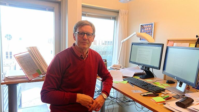En man står vid sitt skrivbord.