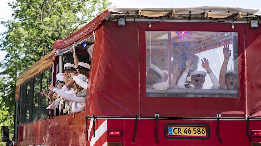 Ungdomar firar studenten i en röd så kallad partybuss.