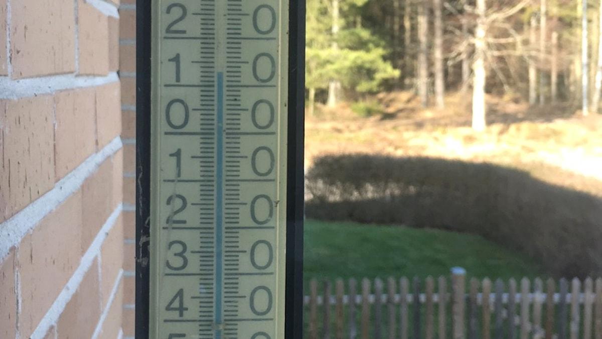 En termometer på en husvägg.